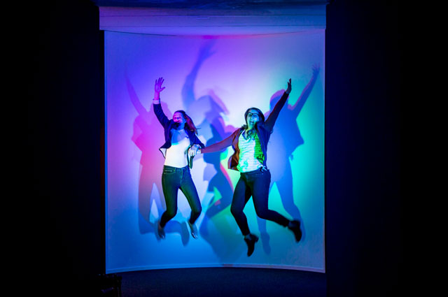 Museum visitors jump in colorful light at Nature's Gift: Humans, Friends and the Unknown at Oakland Museum of California