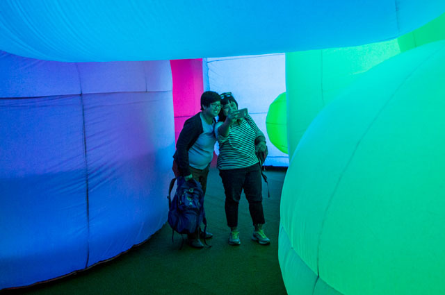 Museum visitors take a selfie inside a colorful glowing inflatable sculpture, Nature's Gift, at Oakland Museum of California