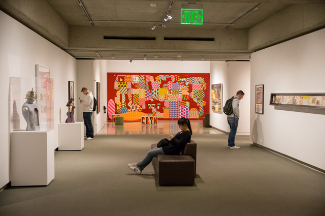 Three people view different sculptures and paintings in the art gallery