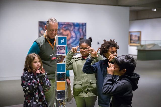 A group of students stand around a tower of blocks in the Gallery of California Art