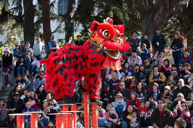A large Chinese dragon costume performance outside in OMCA's 10th street amphitheater while a large crowd watches