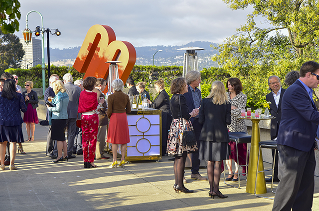 A large group of people gather on the OMCA Gardens patio