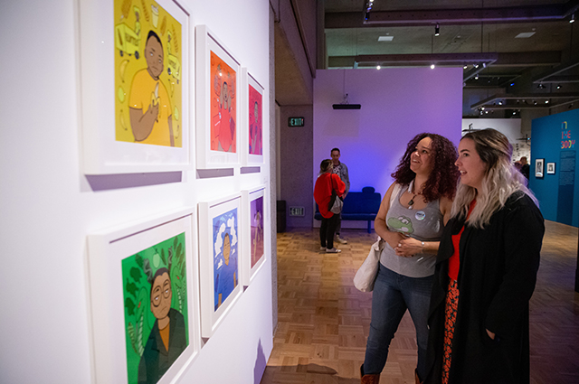 Two women view colorful artwork inside Queer California: Untold Stories