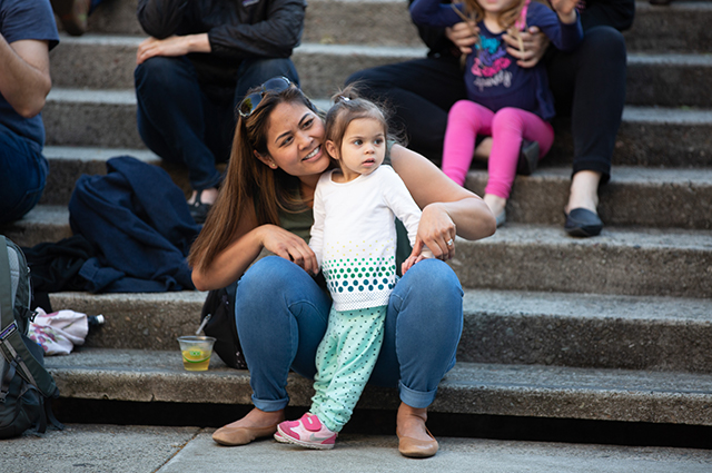 A mom and daughter sit and hug on the 10th street amphitheater steps at Friday Nights at OMCA