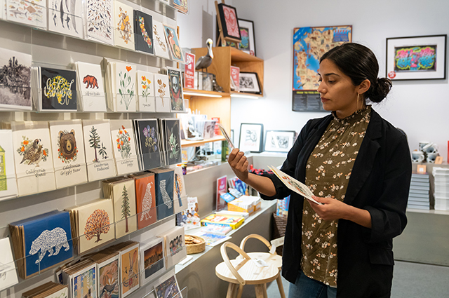 A woman looks at greeting cards in the OMCA Store