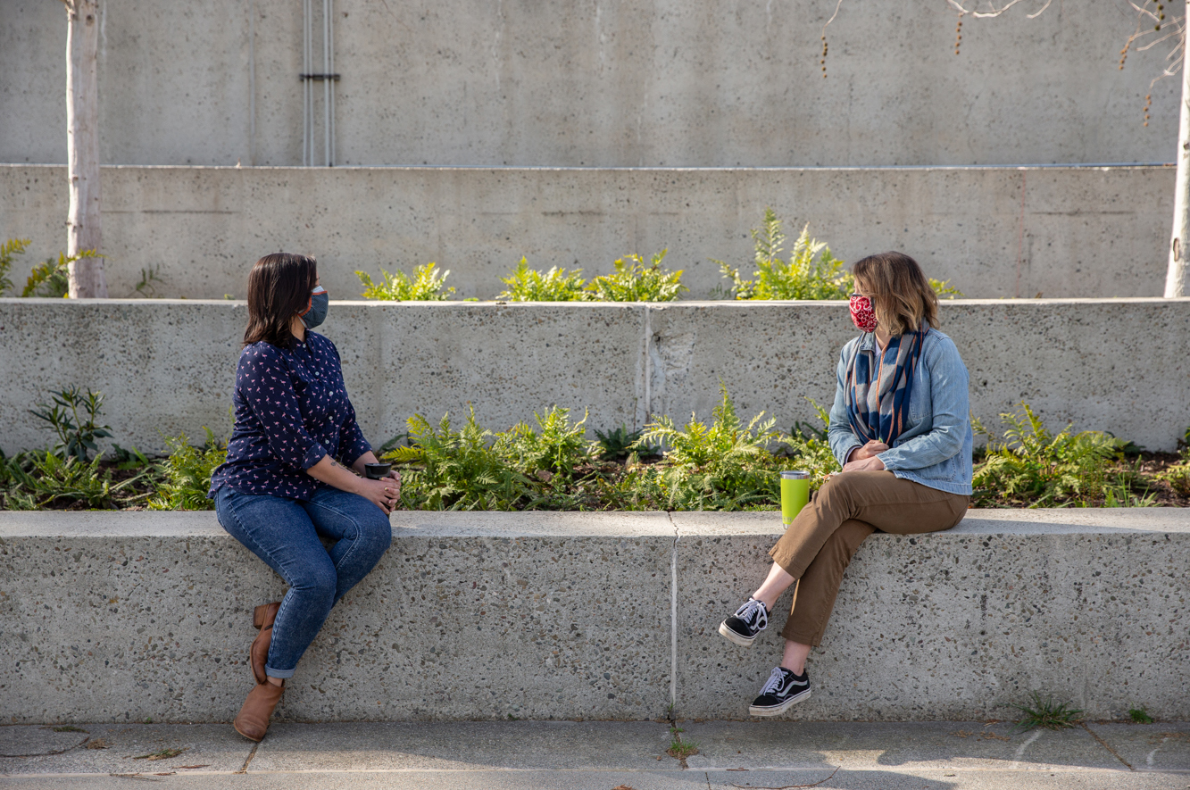 Two women in masks sit in OMCA's newly-renovated Gardens