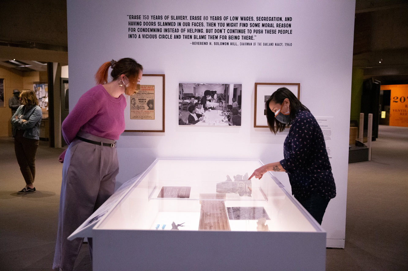 Two women in masks look at objects inside OMCA's Gallery of History Black Panther section