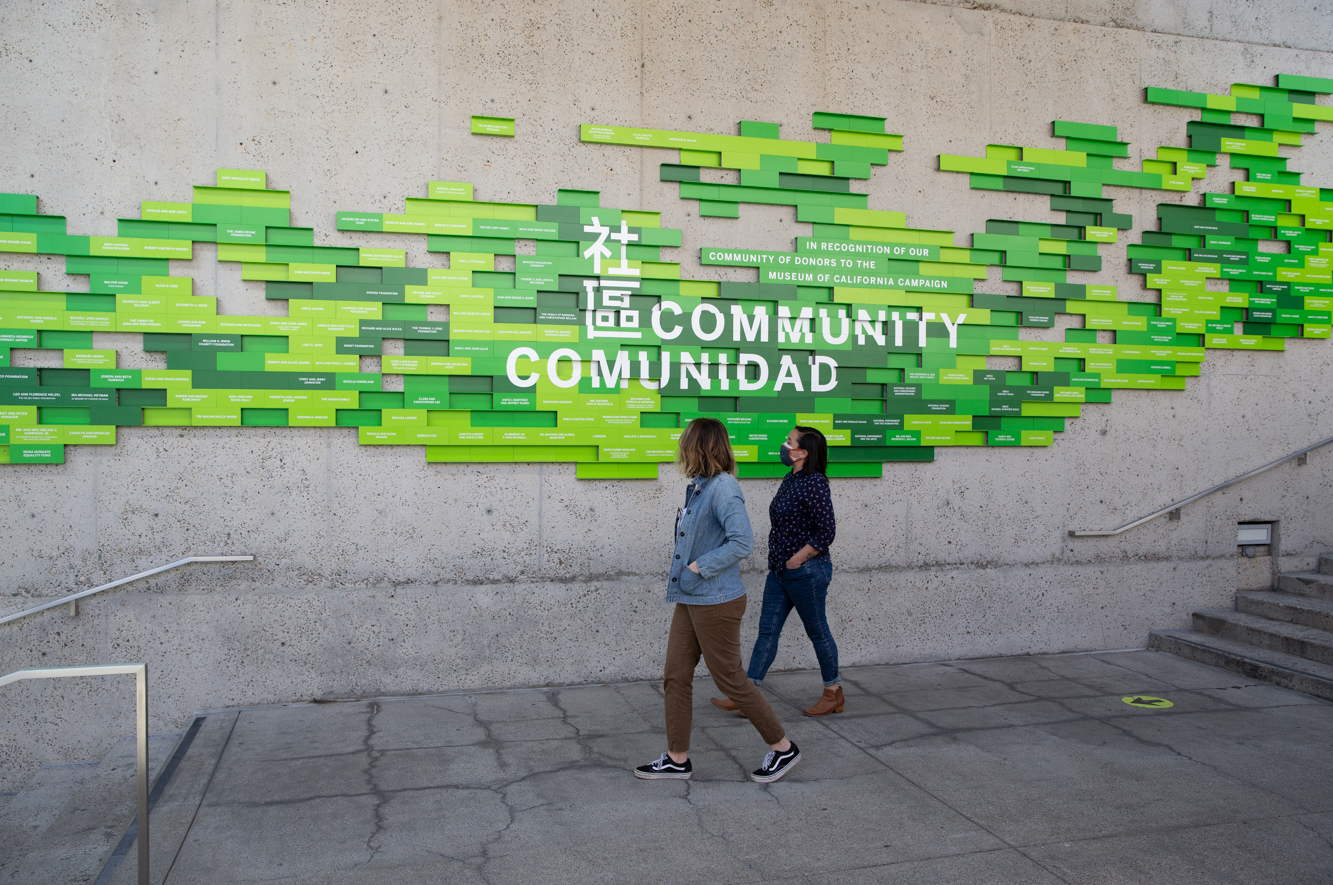 2 people in masks walk past OMCA's Community sign