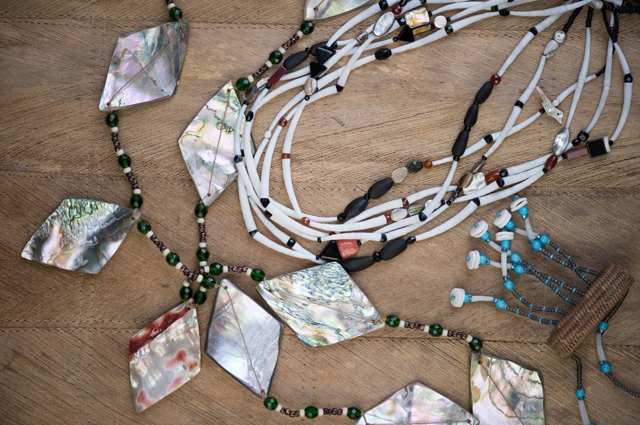 Multicolored necklaces lying on top of a wood table