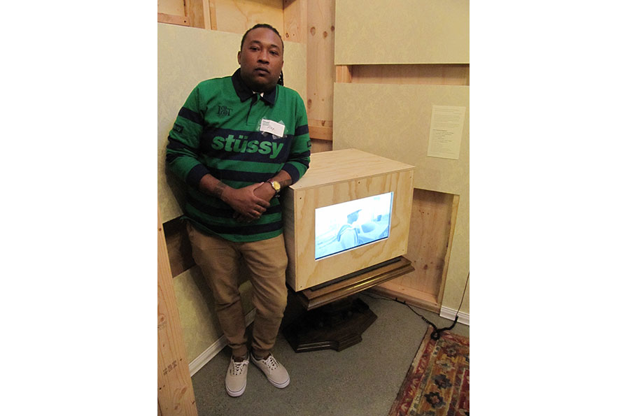 Alex Frantz Ghassan leaning on TV monitor in exhibition Oakland, I want you to know... Photo by Forrealism.com