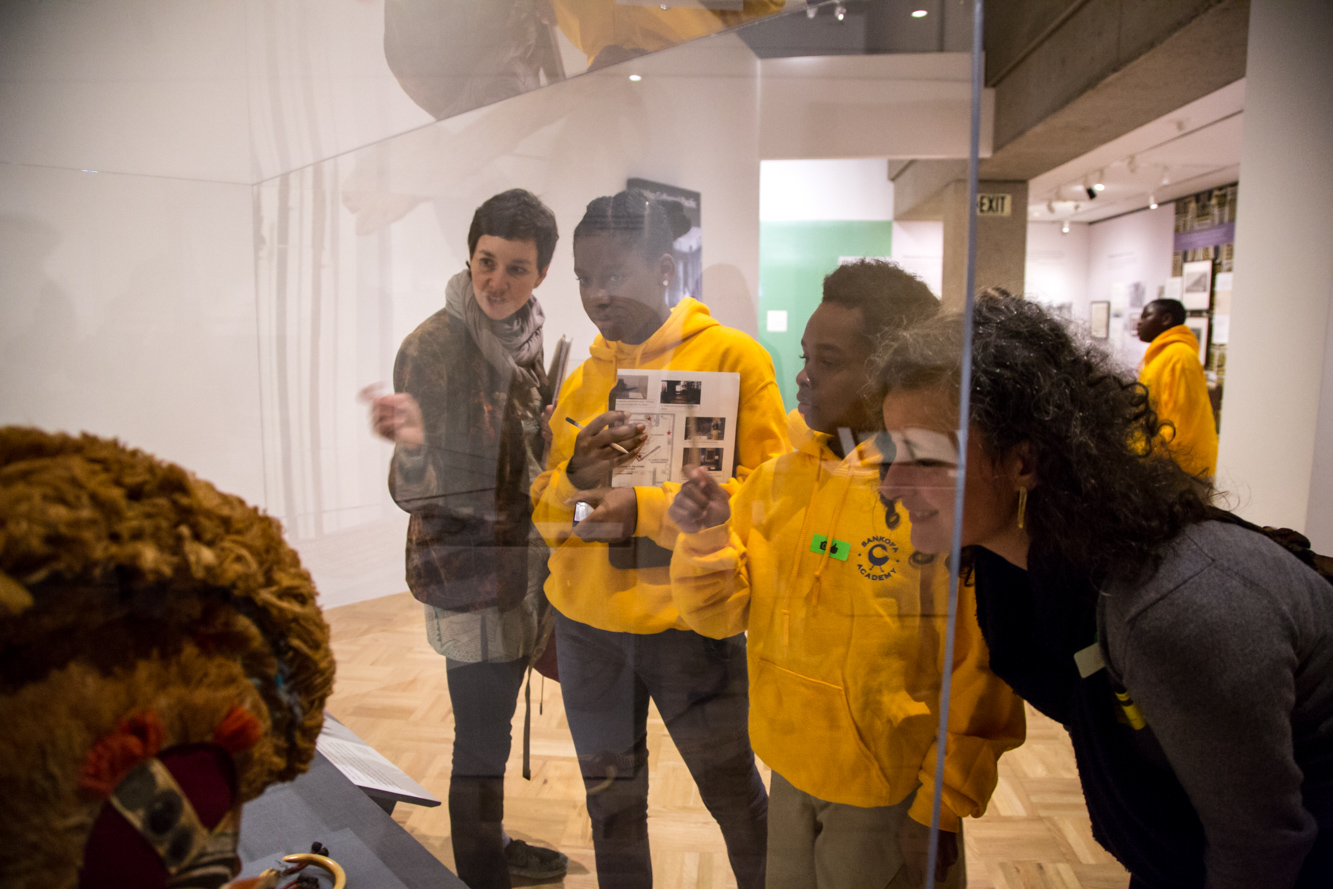 Teenagers looking at artwork through a glass case in a museum