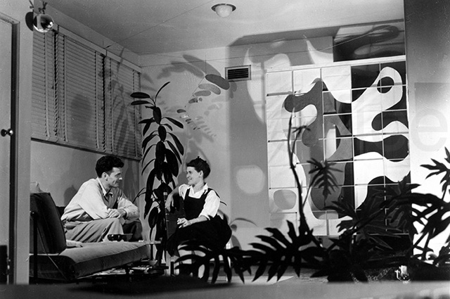 A black and white photo of Charles and Ray Eames sitting and smiling at one another