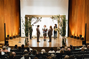 A couple getting married inside the James Moore Theater