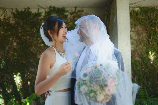 A husband and wife laugh together as the husband wears the wedding veil
