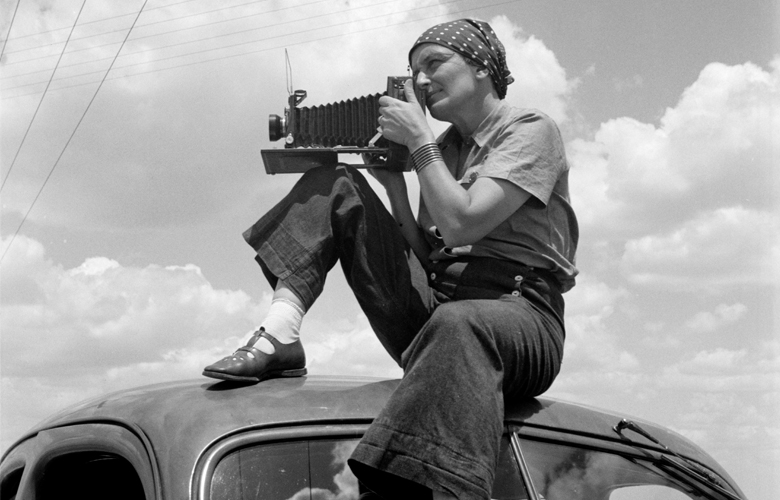 Dorothea Lange holding a camera sitting on top of a car in Texas