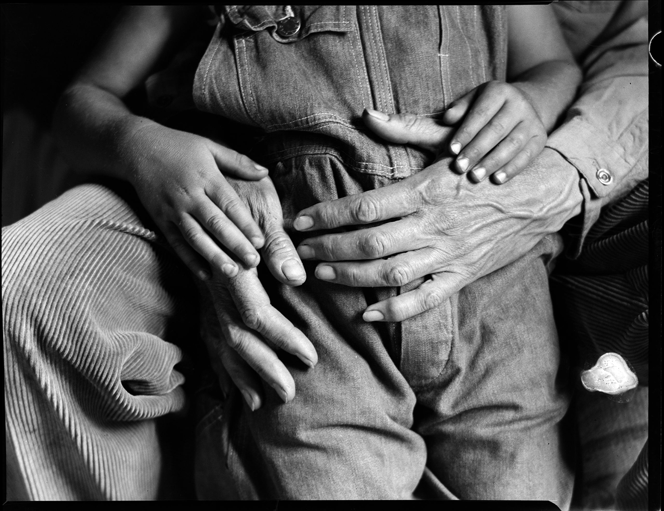 Black and white image of a grown man's hands holding a small child's hands