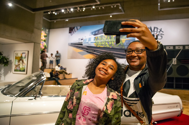 woman and young girl taking a selfie in front of a lowrider