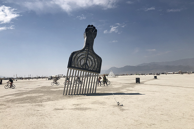 A large sculpture of an afro pick with a fist at the end