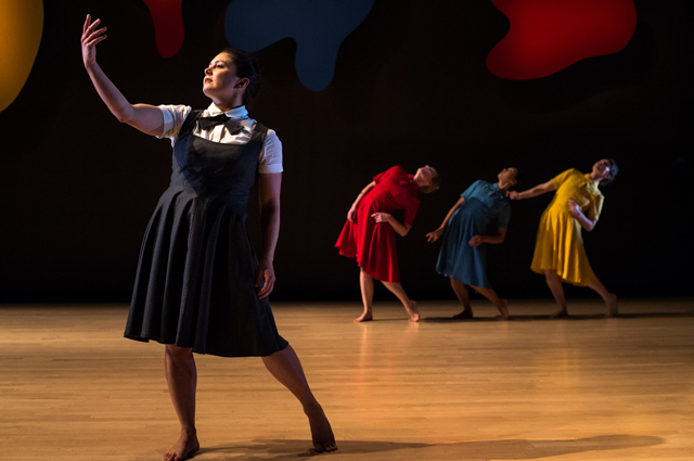 A dancer in a black dress poses while three dancers in red, blue, and yellow dresses pose behind her
