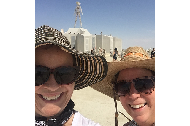 Lori and Kelly take a selfie in front of the burning man