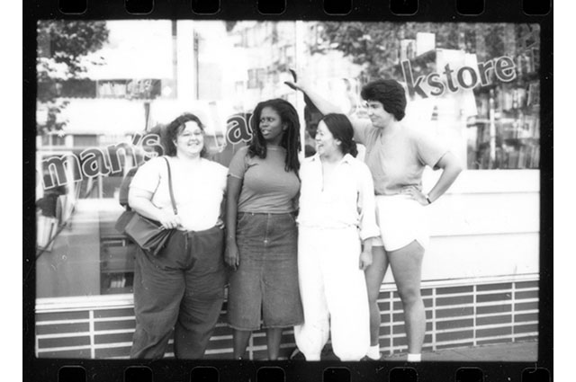 A black and white image of 4 women standing in front of a bookstore window