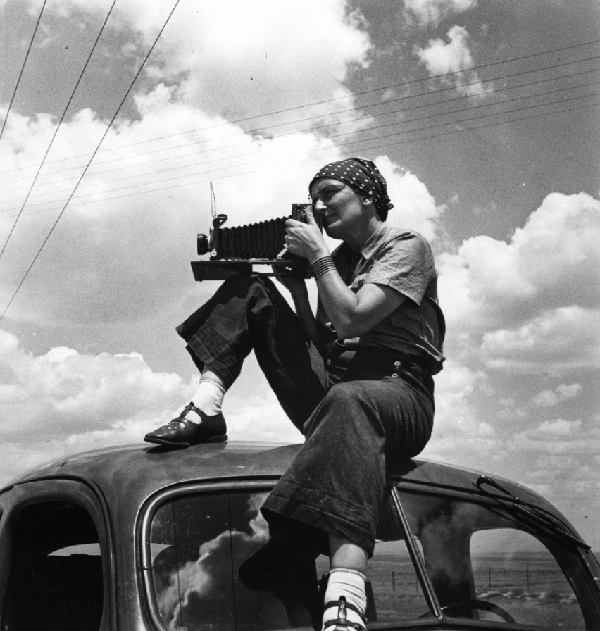 Black and white photo of Dorothea Lange holding a large camera while sitting atop a car