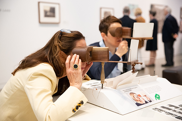 Two women look through photo viewers