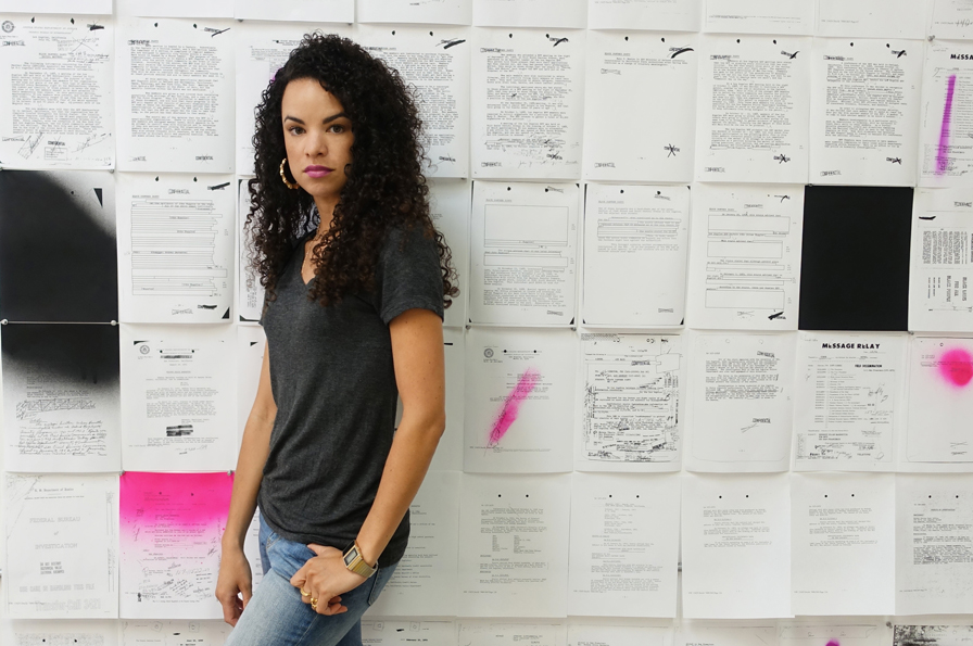 Artist Sadie Barnette in her studio with her installation about her father's FBI file. Courtesy of the artist