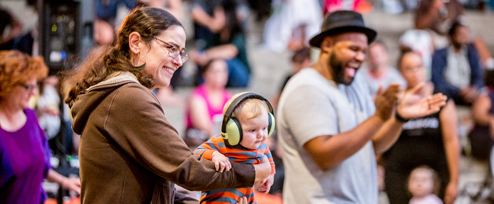 A woman holds a small child wearing comically large headphones at Friday Nights at OMCA