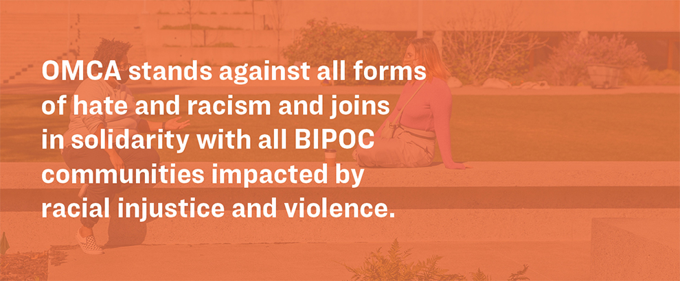 Faded orange image of two people talking with masks on in the OMCA garden. White text on top reads, OMCA stands against all forms of hate and racism and joins in solidarity with all BIPOC communities impacted by racial injustice and violence.