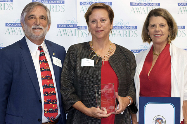 A photo of 3 people smiling at the camera, with Lori Fogarty in the center holding an award