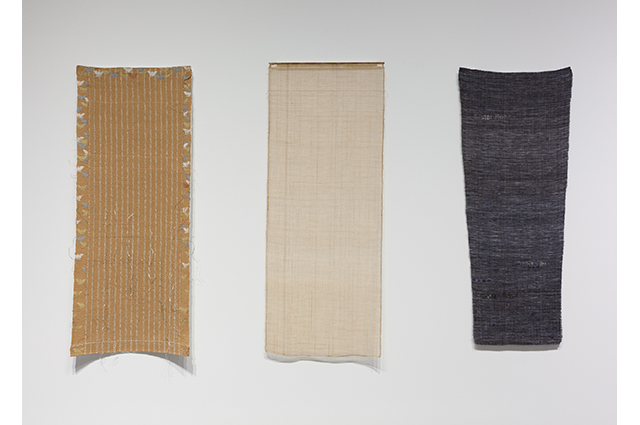 Three tapestries of equal length hang on a white wall