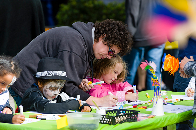 Three children and one adult use markers to draw something for El Dia de los Muertos.