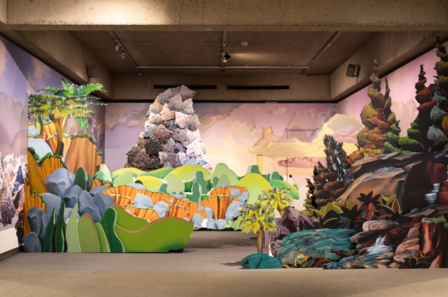 Colorful cartoon-style wooden sculpture of a large mountain and forest scenery