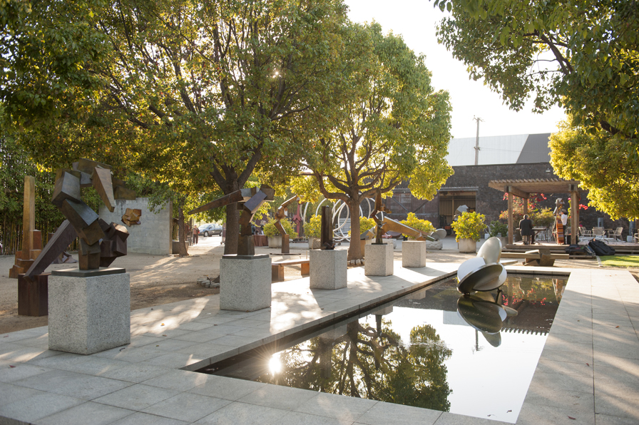The lush sculpture garden and reflecting pool at Bruce Beasley's West Oakland studio complex, site of the future Bruce Beasley Sculpture Center.  Photo: Matthew Reamer. Courtesy of Oakland Museum of California.