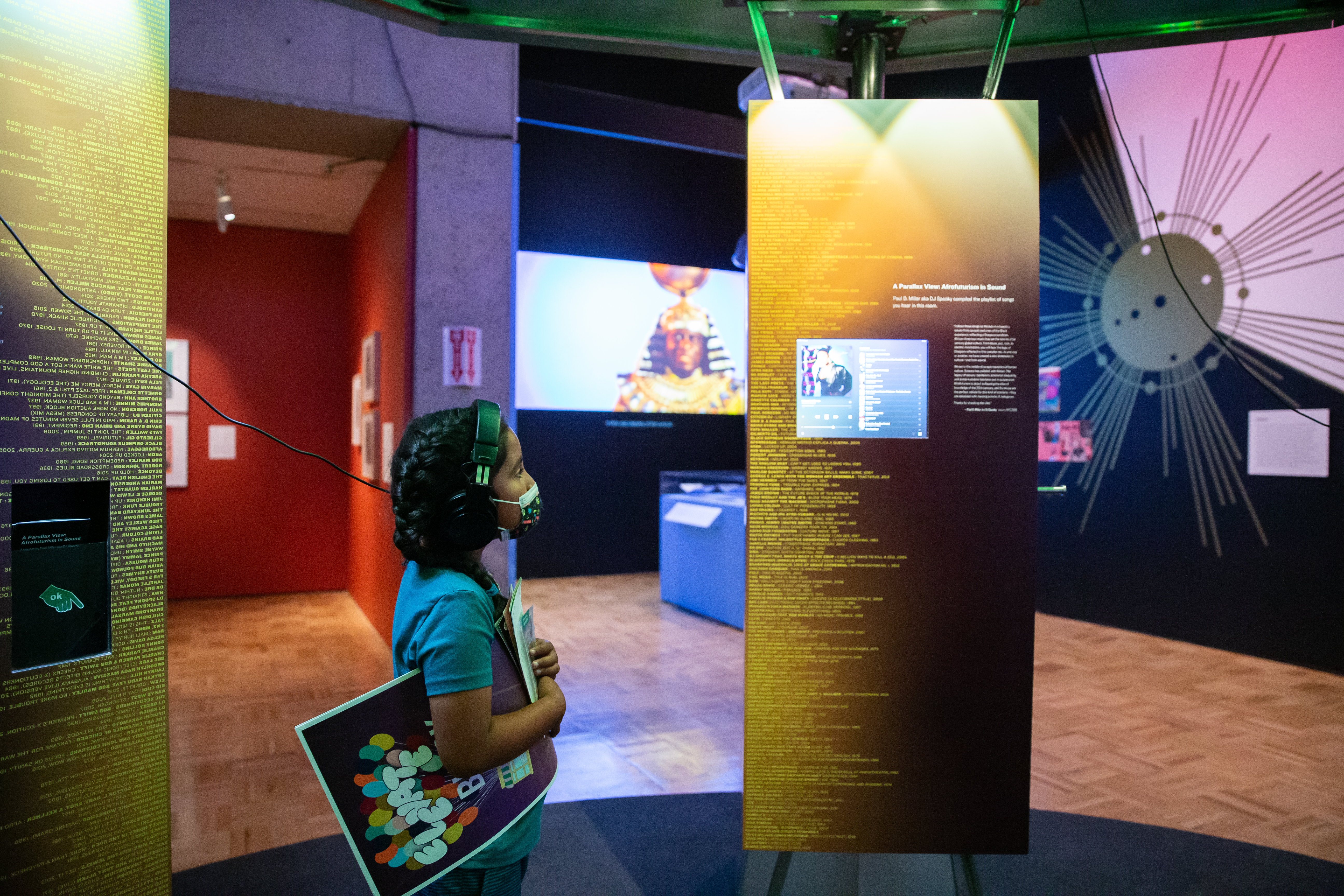 A young girl listens to a playlist by DJ Spooky inside the mothership.