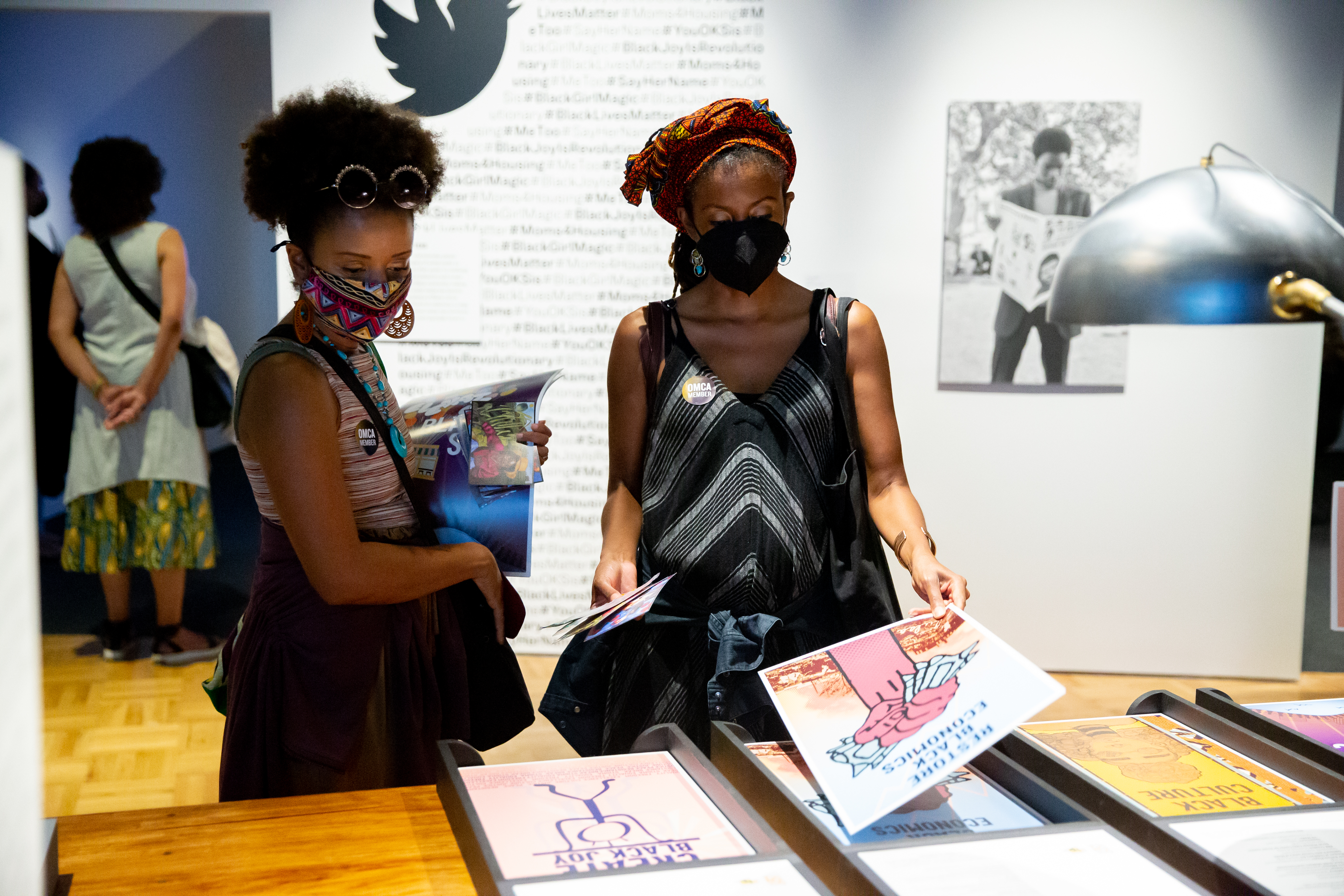 Two women wearing masks collect posters at the Mothership exhibit.