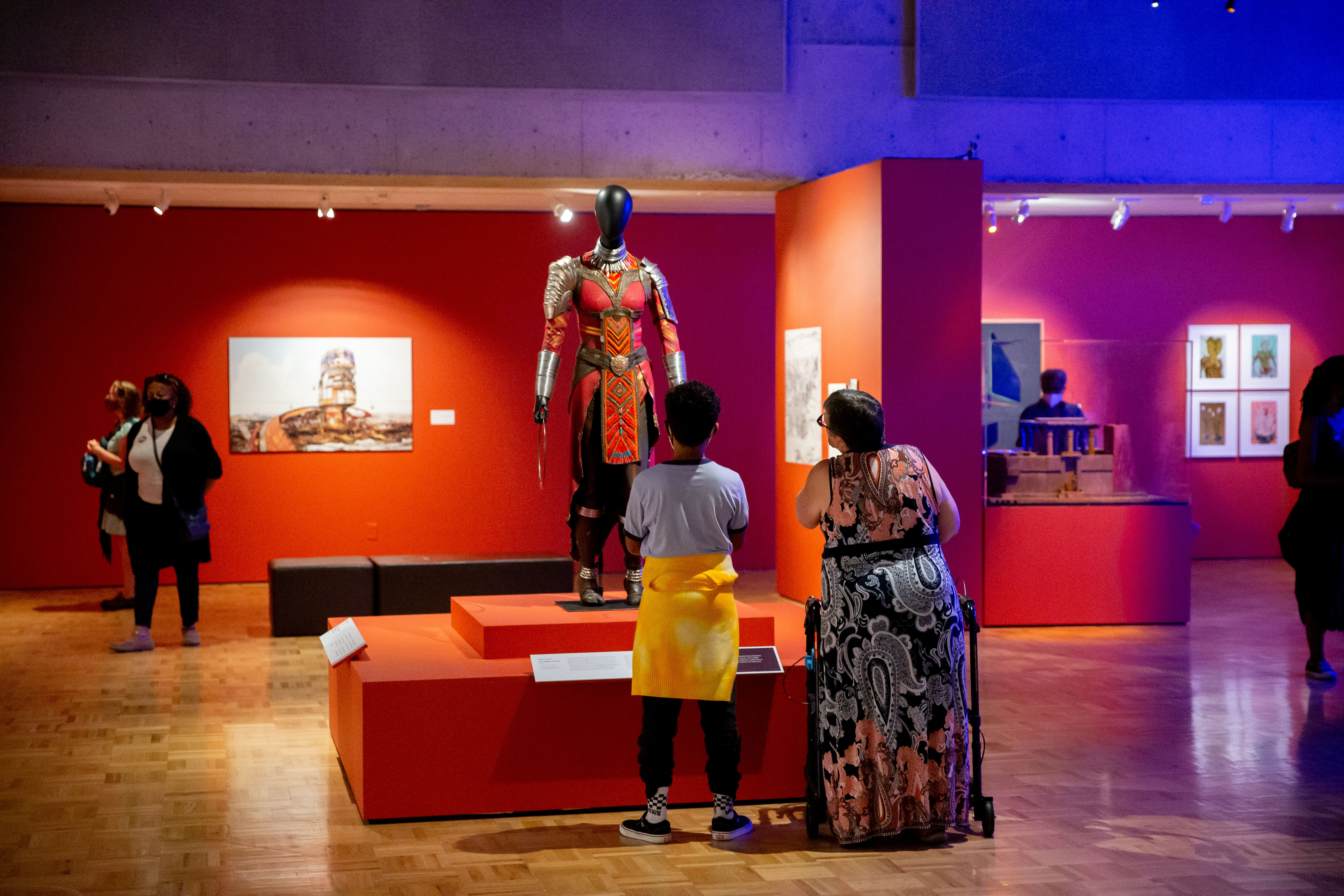 Two people look up at the Dora Milaje Black Panther costume in the Mothership exhibit.