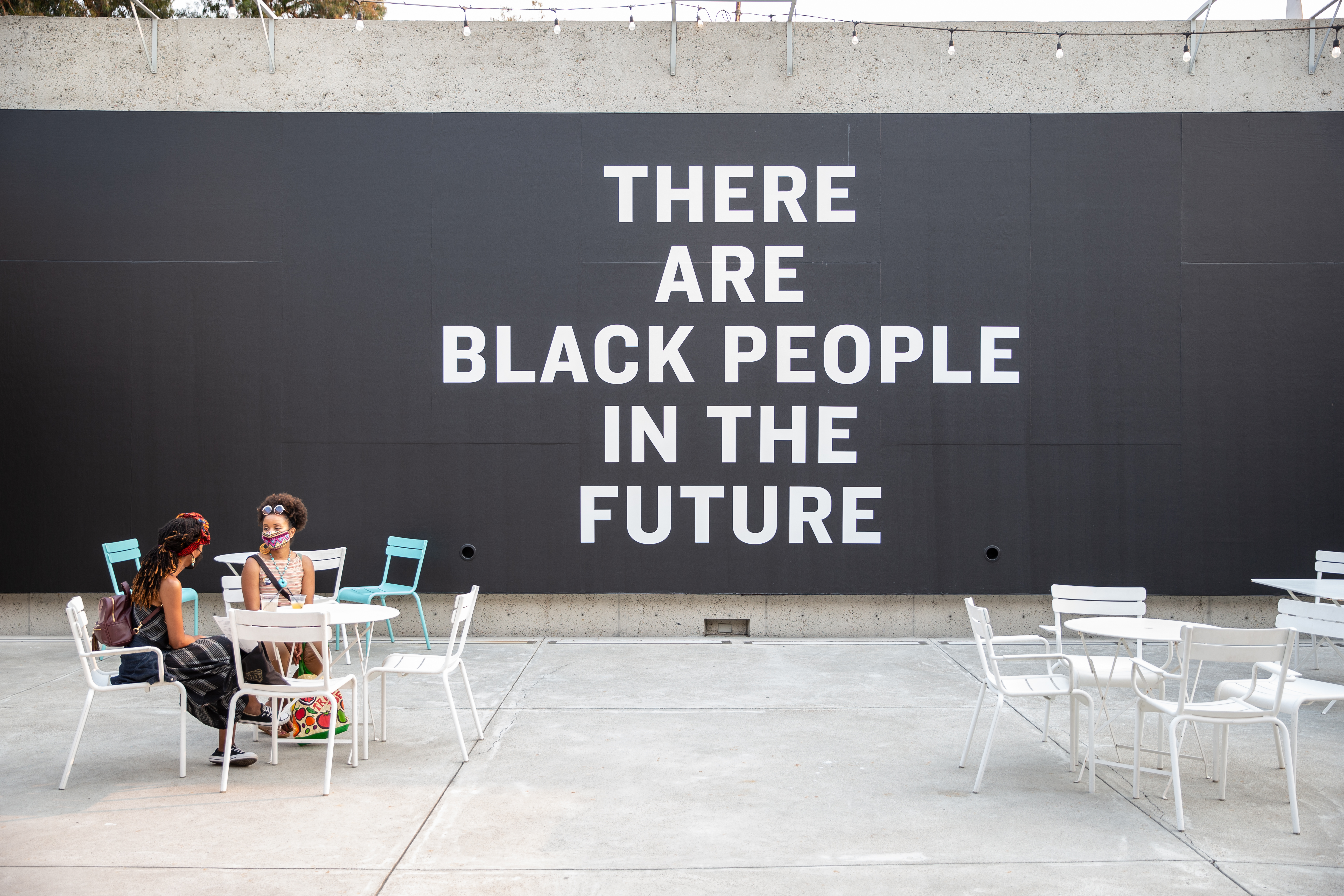 Two women sit at a picnic table in front of the chalkboard wall reading There Are Black People In The Future.