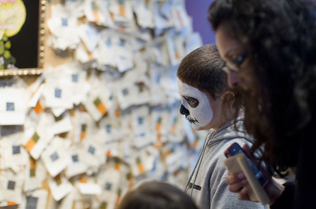 Museum visitors looking at a Days of the Dead installation at the Oakland Museum of California
