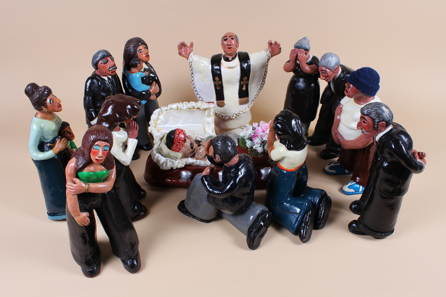 """Richard and Graciela Rios, Velorio/Death of a Homeboy, 1985. Polychrome glazed ceramic, fabric, metal, 11"""" H x 36"""" W x 24"""" D (approx). Courtesy of The Mexican Museum"""