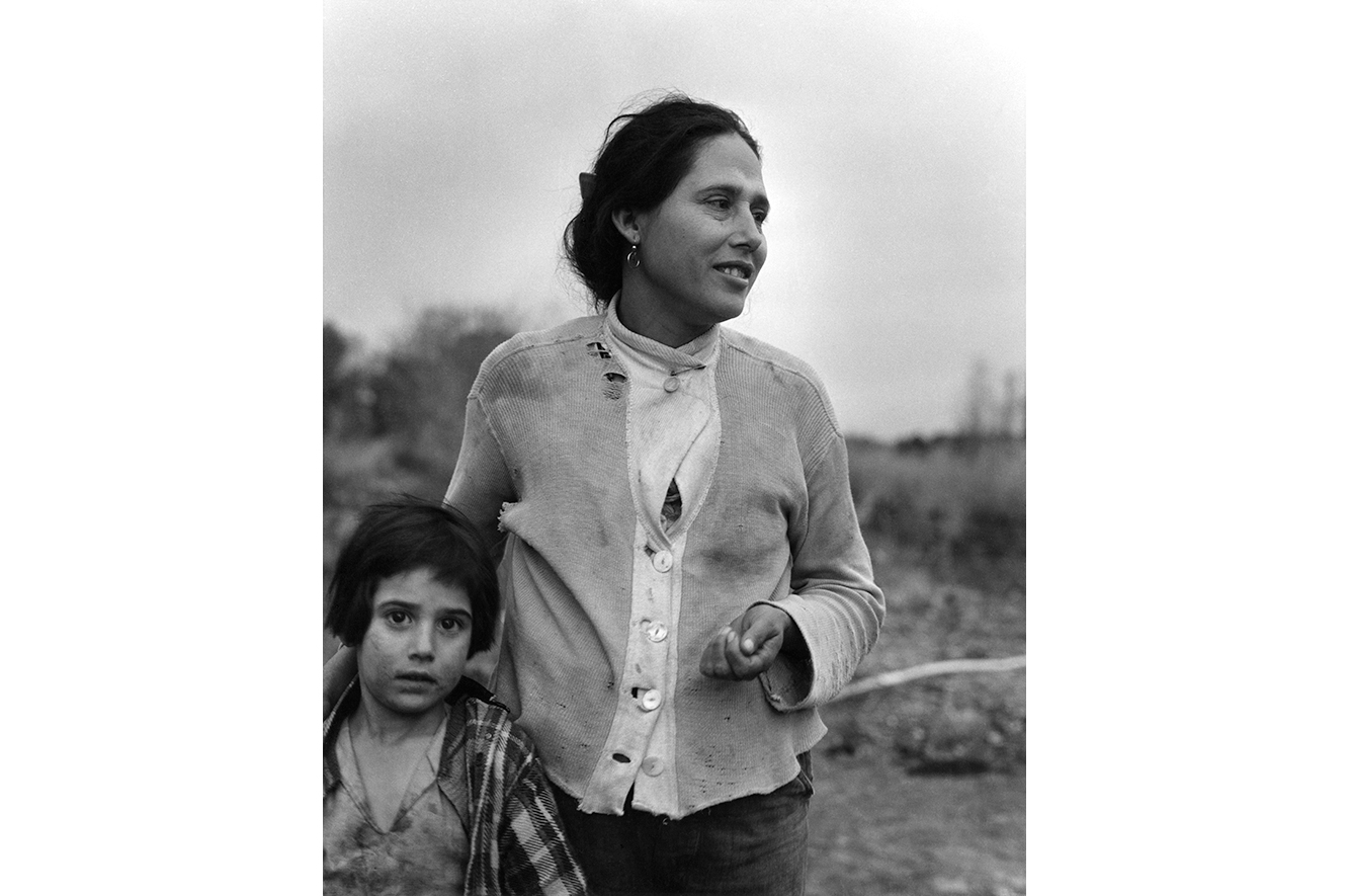 Black and white image of a woman and a child walking in a field in tattered clothes