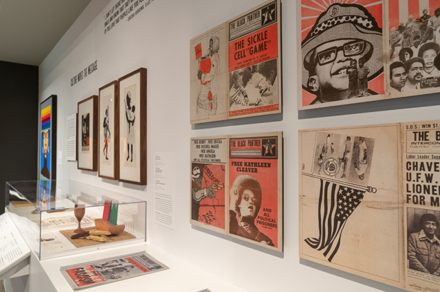 Angled photo of several red, black, and white newspaper covers hanging on the wall