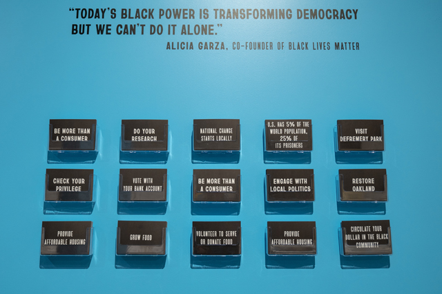 A blue wall with black cards and a quote reading: Today's Black Power is transforming democracy but we can't do it alone. - Alicia Garza, co-founder of Black Lives Matter