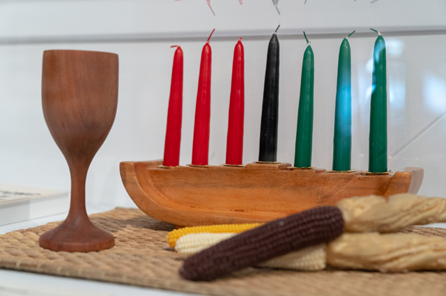 A kwanzaa display with red, black, and green candles, a wooden cup, and multicolored corn