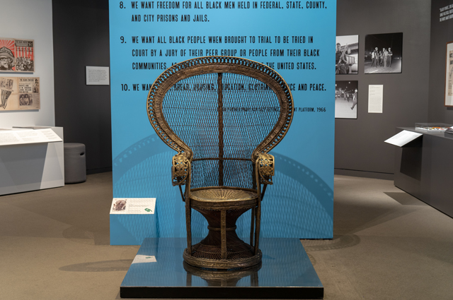 Iconic Huey Newton chair in front of a blue wall with the Black Panther 10 point program in black text