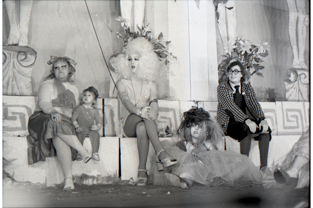 A black and white image of people dressed in drag sitting on a Greek-styled bench