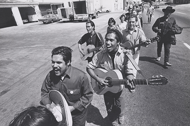 A black and white image of a group of people marching down a street while playing guitars