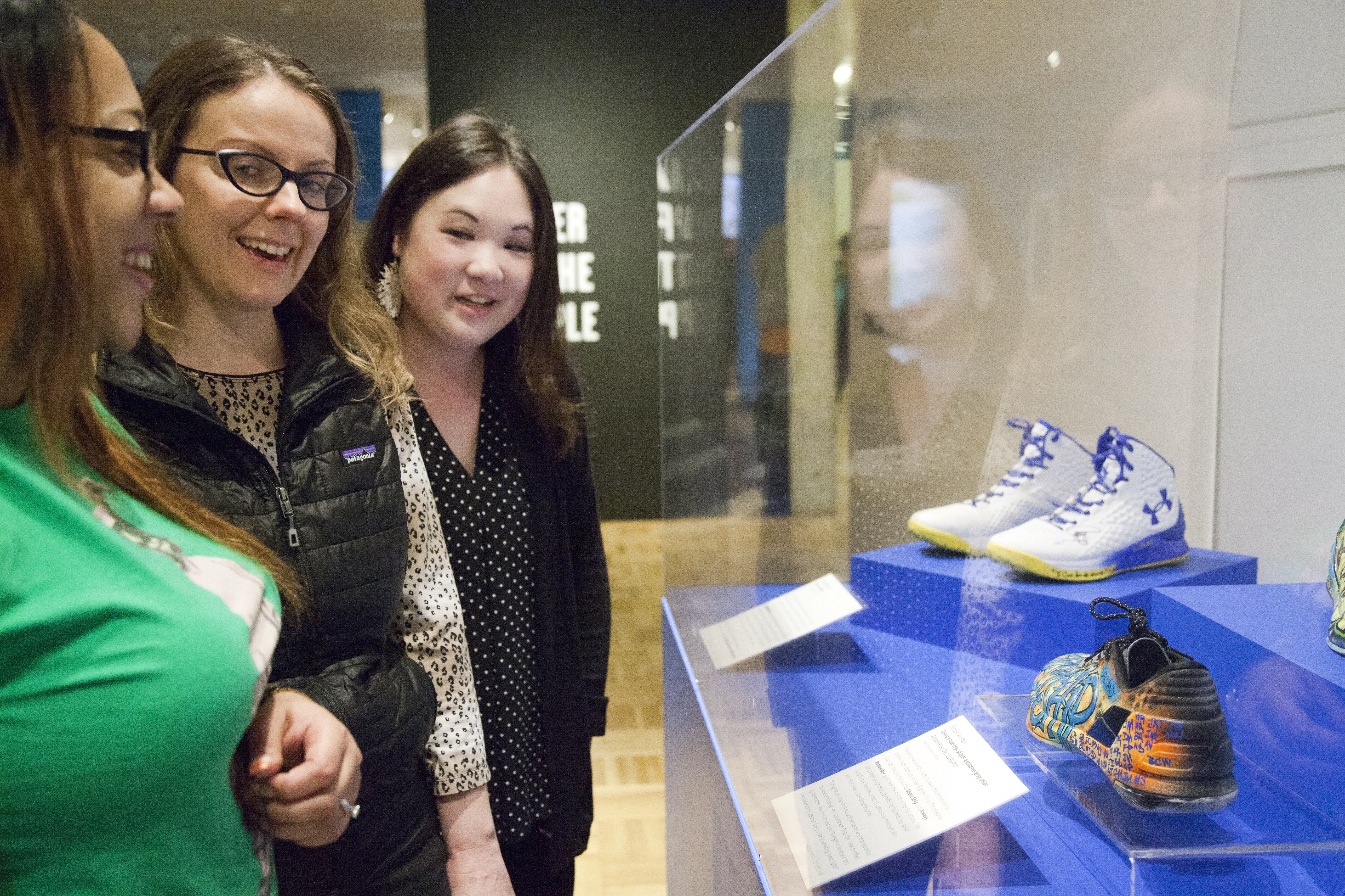 Visitors looking at the Oakland Strong display of Steph Curry's customized sneakers on view at the Oakland Museum of California.