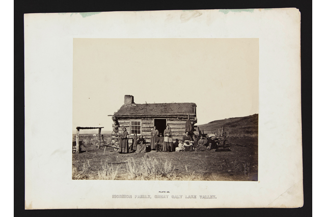 Black and white image of a family standing in front of a small wooden house